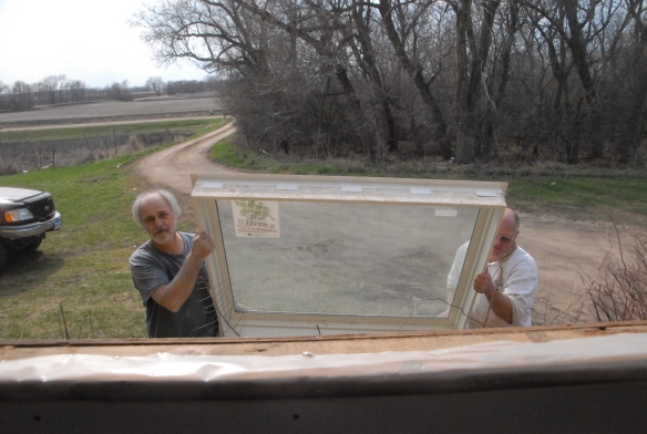 Roger Albright and Steve Bruns bringing the new kitchen window up to install.