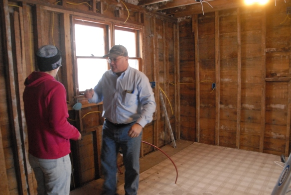 Rebecca and Steve Bruns talking in the kitchen during the remodeling phase. The double hung windows are behind Steve.