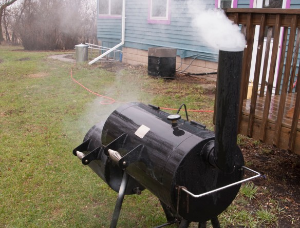 Smoke from the pecan shells escapes through the chimney of our new, secondhand offset smoker.