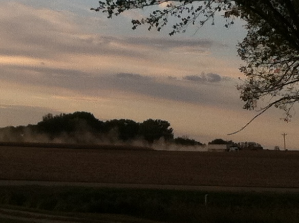 Grain trucks kicked up rolling clouds of dust in the northwest wind
