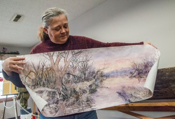 June Lynne holds a drawing of the mural regional artist Malena Handeen will paint as part of the dugout canoe display.